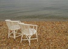 2 белых пустых стуль на Pebble Beach Стоковые Фото