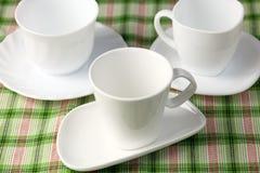 3 белых пустых чашки и поддонника на зеленой предпосылке Стоковое Изображение