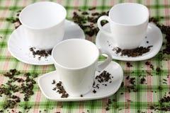 3 белых пустых чашки и поддонника с разлитыми листьями зеленого чая Стоковое Изображение RF