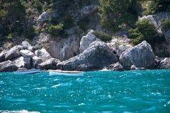 2 белых рыбацкой лодки танцуя на море развевают близрасположенный скалистый ба Стоковые Изображения
