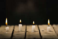 4 белых свечи воска сидя на деревянной поверхности горя с черной предпосылкой, красивой светлой установкой Стоковая Фотография RF