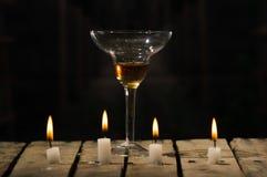 4 белых свечи сидя на деревянном поверхностном горении, стекло воска коктеиля помещенное позади, черная предпосылка Стоковые Фотографии RF