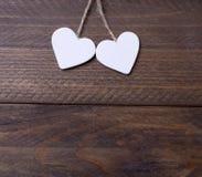 2 белых сердца на коричневом деревянном столе Стоковые Фотографии RF