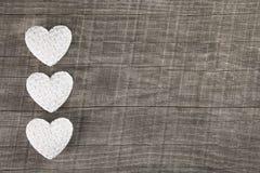 3 белых сердца на старой серой коричневой деревянной предпосылке Стоковая Фотография