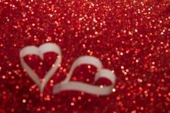2 белых сердца от бумаги на красной сияющей запачканной предпосылке Стоковые Изображения