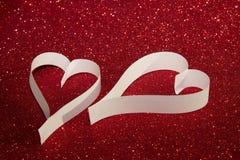 2 белых сердца от бумаги на красной сияющей предпосылке Стоковая Фотография RF