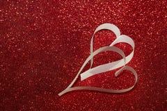 2 белых сердца от бумаги на красной сияющей предпосылке Стоковое Изображение RF