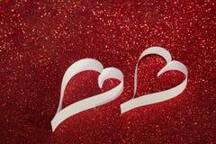 2 белых сердца от бумаги на красной сияющей предпосылке Стоковые Изображения RF