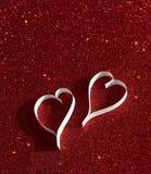 2 белых сердца от бумаги на красном сияющем backround Стоковая Фотография
