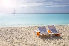 2 белых стуль с оранжевыми полотенцами на пляже Стоковое фото RF