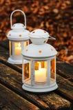2 белых фонарика на деревянной скамье Стоковые Фото