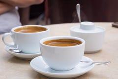 2 белых чашки кофе, шар сахара на мраморной таблице Стоковое Изображение RF