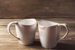 2 белых чашки, одного из их носят губную помаду, отношение людей и женщин, на предпосылке старое деревянного Стоковые Изображения RF