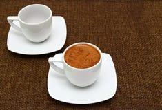 2 белых чашки с греческим кофе на предпосылке увольнения Стоковое Изображение
