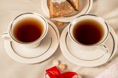 2 белых чашки с яблочным пирогом красная тесемка Стоковая Фотография