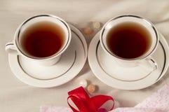 2 белых чашки чаю и красного смычок Стоковые Фотографии RF