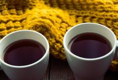 2 белых чашки чаю и шарфа на старом деревянном столе Стоковые Изображения RF