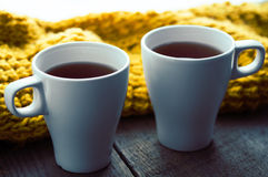 2 белых чашки чаю и шарфа на старом деревянном столе Стоковое фото RF