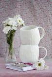 2 белых чашки, offlowers букета и тетрадь Стоковые Изображения
