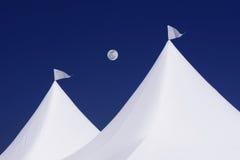 2 белых шатра с флагами парламентера, полнолунием и глубоким голубым небом Стоковое фото RF