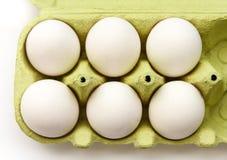 6 белых яичек в открытом зеленом пакете, осмотренном от верхней части Стоковые Фотографии RF