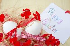 2 белых яичка в гнезде с цветками и карточкой Стоковые Изображения RF