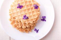 Бельгийские waffles на белой плите на деревянной предпосылке украсили фиолетовый цветок Взгляд сверху Стоковая Фотография