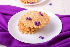 Бельгийские waffles на белой плите на деревянной предпосылке украсили фиолетовый цветок Стоковая Фотография