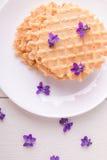 Бельгийские waffles на белой плите на деревянной предпосылке украсили фиолетовый цветок Взгляд сверху Стоковое фото RF