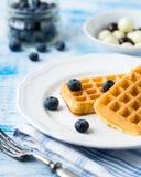 Бельгийские waffles на белой плите на свете - голубой предпосылке Стоковое фото RF