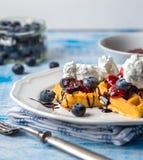 Бельгийские waffles на белой плите на свете - голубой предпосылке Стоковые Изображения