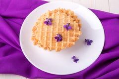Бельгийские waffles на белой плите украсили фиолетовый цветок Взгляд сверху Стоковая Фотография RF