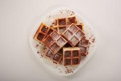 Бельгийские waffles с заскрежетанными шоколадом и замороженностью на белой плите Стоковое фото RF