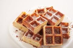 Бельгийские waffles с заскрежетанными шоколадом и замороженностью на белой плите Стоковое Изображение