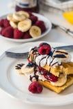 Бельгийские waffles с полениками и бананами на белой плите и Стоковое Изображение RF