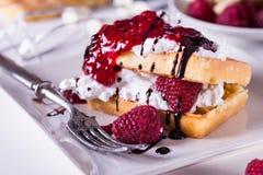 Бельгийские waffles с полениками и двойной сливк на белой плите Стоковое фото RF