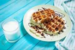 Бельгийские waffles для завтрака на голубой таблице Стоковая Фотография