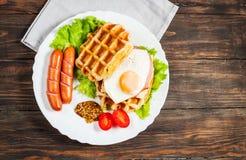 Бельгийский waffle с яичком и сосиской на деревянной таблице Стоковое фото RF