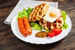 Бельгийский waffle с яичком и сосиской на деревянной таблице Стоковые Фотографии RF