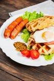 Бельгийский waffle с яичком и сосиской на деревянной таблице Стоковое Изображение RF