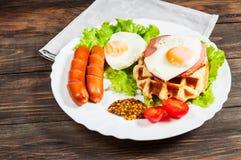 Бельгийский waffle с яичком и сосиской на деревянной таблице Стоковое Фото