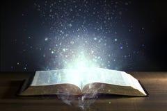 Библия открытая с накаляя светами стоковое фото rf