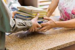 Библиотекарь принимая книги от мальчика на счетчик библиотеки стоковое изображение rf