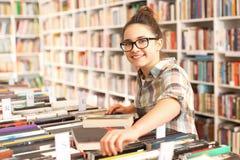 Библиотека, подросток выбирает книгу Стоковая Фотография