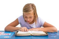 Библия чтения маленькой девочки на голубом столе Стоковая Фотография