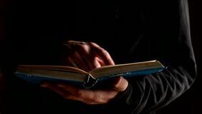 Библия чтения человека открытая в темной комнате, религиозной концепции сток-видео