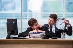 2 бизнесмена близнецов споря друг с другом над крайним сроком Стоковые Фотографии RF