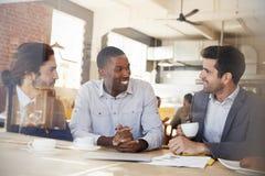3 бизнесмена встречая в кофейне снятой через окно Стоковое фото RF