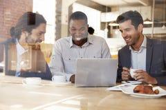 3 бизнесмена встречая в кофейне снятой через окно Стоковое Изображение RF
