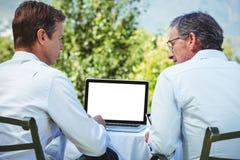 2 бизнесмена встречая в ресторане используя компьтер-книжку Стоковая Фотография